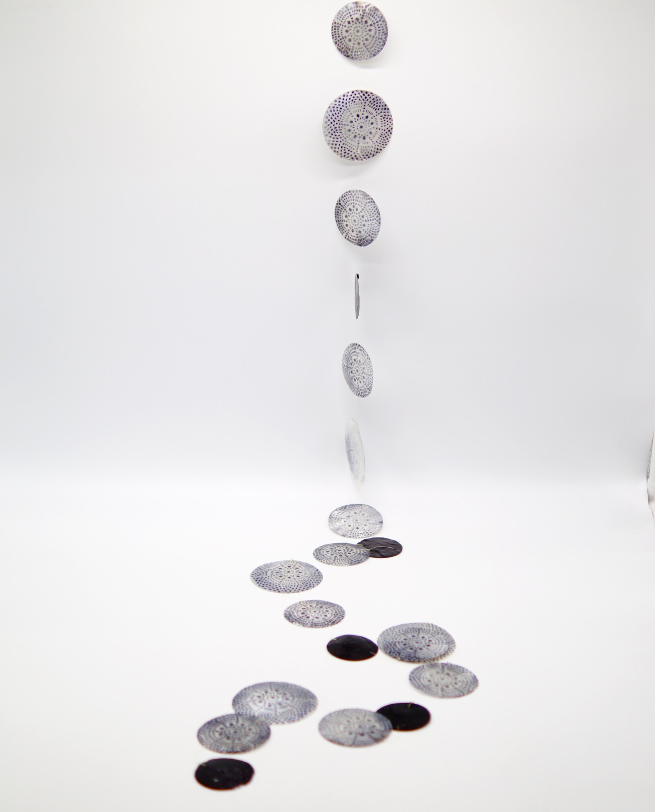 Garland of mother of pearl painted into a mix of patterns with black dots